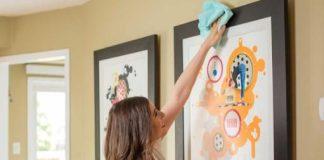 γυναίκα ξεσκονίζει πίνακες στον τοίχο