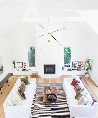 Άσπροι καναπέδες σε σαλόνι με τζάκι