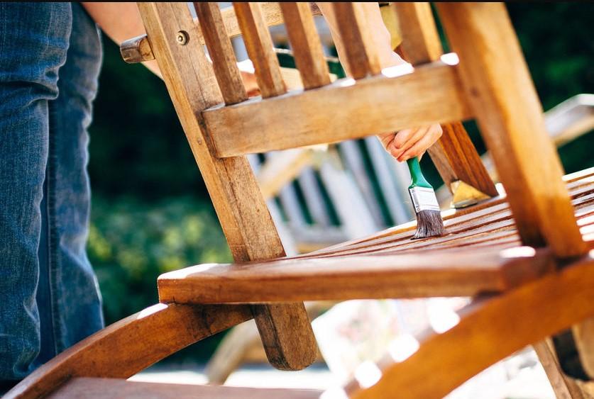 άντρας βάφει ξύλινη καρέκλα