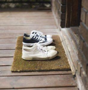 παπούτσια στο χαλάκι της εξώπορτας του σπιτιού