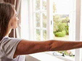 γυναίκα ανοίγει παράθυρο εξαερισμός σπιτιού