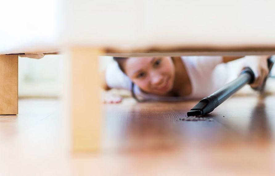 γυναίκα καθαρίζει το κάτω μέρος από το κρεβάτι