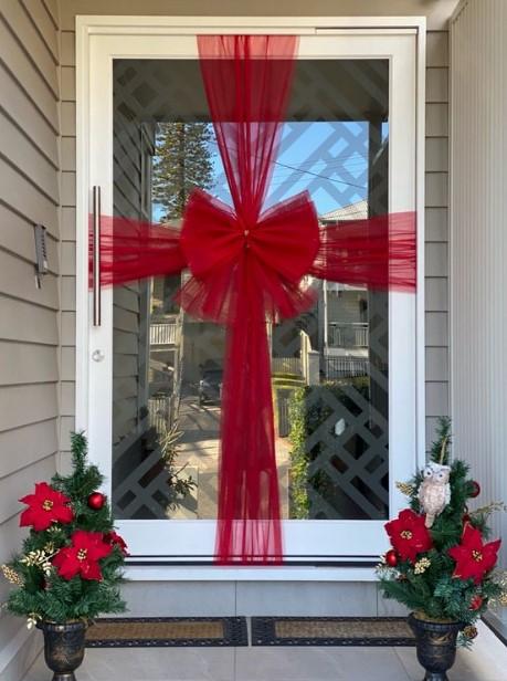 χριστουγεννιάτικη διακόσμηση πόρτας με κορδέλα
