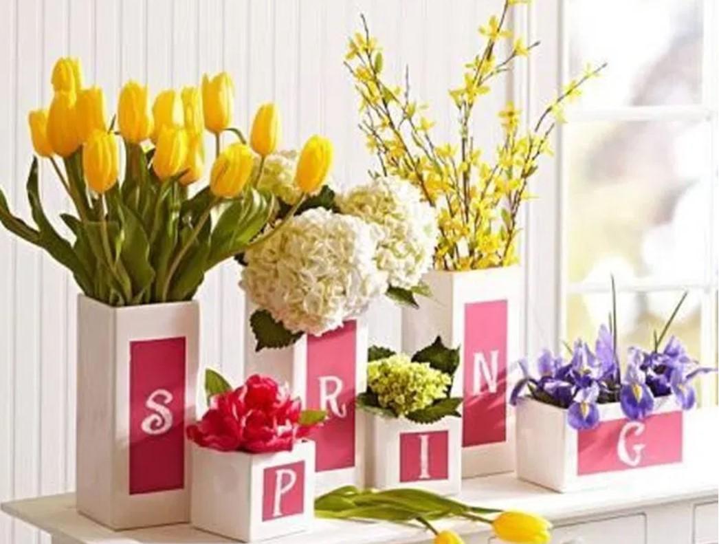 ανισόπεδα βάζα με διαφορετικά χρωματιστά λουλούδια