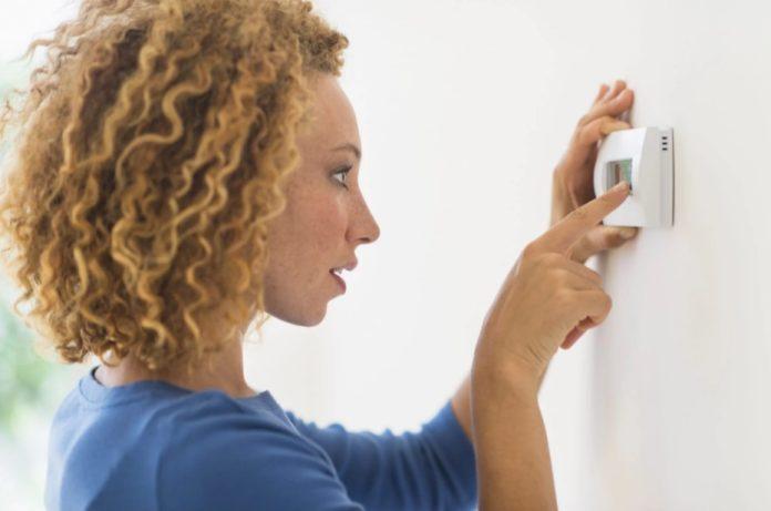 γυναίκα ρυθμίζει θερμοστάτη